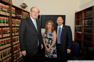"[""Senator John D. (Jay) Rockefeller stands beside two unidentified individuals in an office library.""]%"