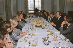 "[""Senator John D. (Jay) Rockefeller sits at a banquet table with numerous unidentified individuals during an AEP reception.""]%"