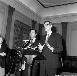 "[""Senator John D. (Jay) Rockefeller speaks behind a podium with Senator John Heinz standing beside him.""]%"