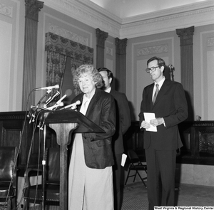 "[""Senator John D. (Jay) Rockefeller and Senator John Heinz stand behind a podium where an unidentified woman speaks about the Dislocated Workers Improvement Act.""]%"