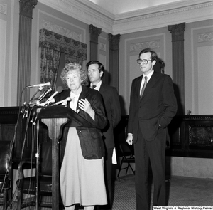 "[""An unidentified woman speaks about the Dislocated Workers Improvement Act of 1987 as Senator John D. (Jay) Rockefeller and Senator John Heinz stand behind her.""]%"