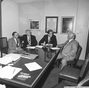 "[""Senator John D. (Jay) Rockefeller sits with three unidentified men at a conference table in his office.""]%"