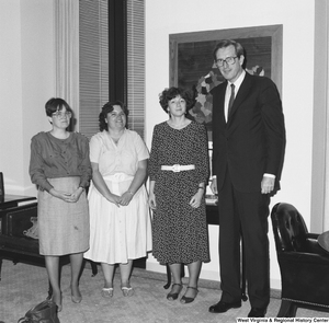 "[""Senator John D. (Jay) Rockefeller stands next to three unidentified women in his office.""]%"