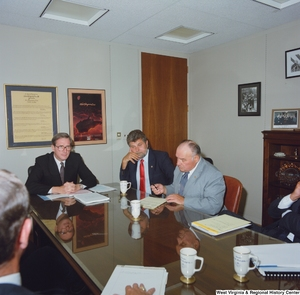 "[""Senator John D. (Jay) Rockefeller listens to another man speak during a meeting in his office.""]%"