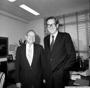 "[""Senator John D. (Jay) Rockefeller stands in front of the desk in his office and poses for a photograph with an unidentified man.""]%"