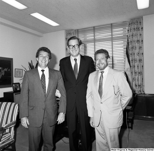 "[""Senator John D. (Jay) Rockefeller links arms with two unidentified individuals in his office and poses for a photograph.""]%"