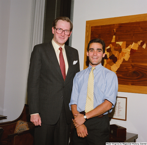 "[""Senator John D. (Jay) Rockefeller stands next to a young man who appears to be an intern.""]%"