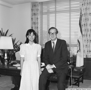 "[""Senator John D. (Jay) Rockefeller sits on the corner of the desk in his office and poses for a photograph with an unidentified individual.""]%"