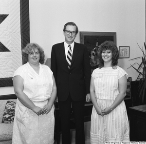 "[""Two unidentified individuals pose for a photograph with Senator John D. (Jay) Rockefeller in his Washington office.""]%"