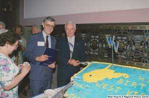 "[""Senator Robert C. Byrd cuts a cake that celebrates the birthday of the state of West Virginia.""]%"