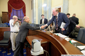"[""Senator John D. (Jay) Rockefeller shakes hands with an unidentified man after a Commerce Committee hearing.""]%"