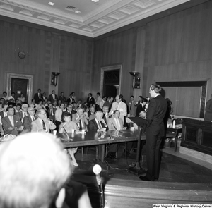 "[""Senator John D. (Jay) Rockefeller addresses a large audience in one of the Senate committee hearing rooms.""]%"