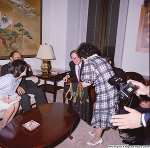 "[""Senator John D. (Jay) Rockefeller looks at fabric that a woman is showing him during a meeting with representatives from the Japanese Embassy.""]%"