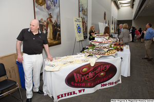 "[""A man stands at a table for the Wyckedley Good Cupcakes at an event to celebrate the 150th birthday of West Virginia.""]%"