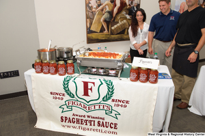 "[""Three people stand behind a table for the Figaretti's Spaghetti Sauce company at the celebration for West Virginia's 150th birthday.""]%"