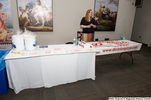 "[""A woman stands at a table for DiCarlo's Pizza at the 150th birthday celebration for West Virginia.""]%"