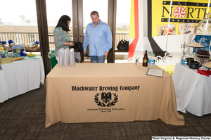 "[""A man stands behind the Blackwater Brewing Company table at the 150th birthday celebration for West Virginia.""]%"