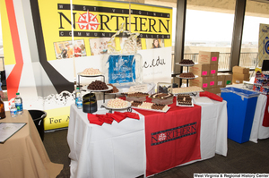 "[""The West Virginia Northern Community College has a table of chocolates at the 150th birthday celebration for West Virginia.""]%"