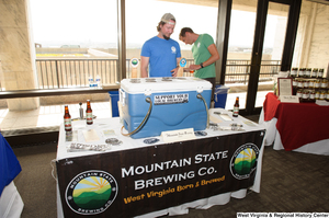 "[""Two men stand behind the Mountain State Brewing Company table at the 150th birthday celebration for West Virginia.""]%"