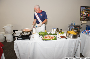 "[""A man cooks shrimp at the 150th birthday celebration for West Virginia.""]%"