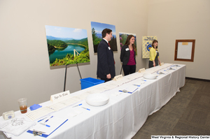 "[""Three people stand behind the sign in table for the 150th birthday celebration for West Virginia.""]%"