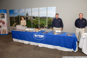 "[""People stand behind the West Virginia Department of Tourism table at the state's 150th birthday celebration.""]%"