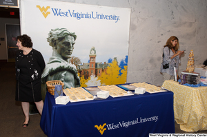 "[""A woman stands behind the West Virginia University table at the state's 150th birthday celebration.""]%"