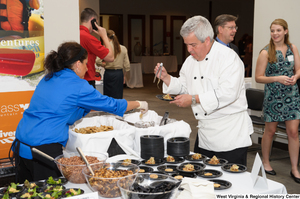 "[""A chef prepares food at the 150th birthday celebration for West Virginia.""]%"