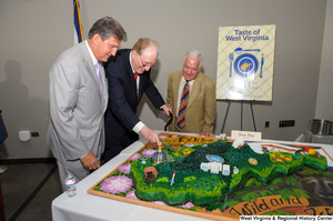 "[""Senator John D. (Jay) Rockefeller cuts the West Virginia birthday cake during the state's 150th birthday celebration.""]%"