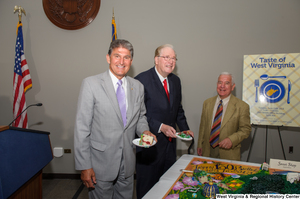 "[""Senators John D. (Jay) Rockefeller and Joe Manchin hold pieces of cake during the 150th birthday celebration for West Virginia.""]%"