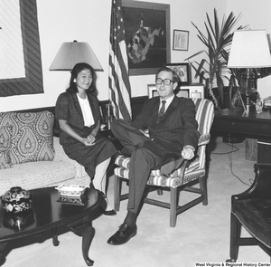 "[""Senator John D. (Jay) Rockefeller sits on a chair in his office with one of his summer interns.""]%"