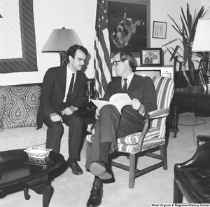 "[""Senator John D. (Jay) Rockefeller flips through a document and speaks with an unidentified man in his office.""]%"
