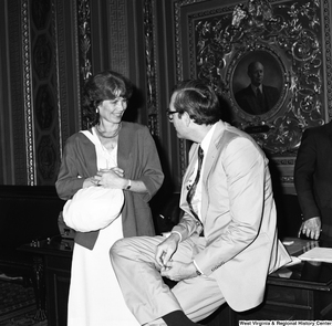 "[""Senator John D. (Jay) Rockefeller speaks to an unidentified woman in the President's Room outside the Senate.""]%"