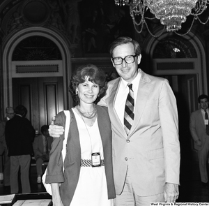 "[""Senator John D. (Jay) Rockefeller poses for a photograph in the Senate with an unidentified woman wearing a \""NASA Headquarters\"" badge.""]%"
