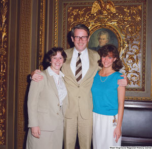 "[""Senator John D. (Jay) Rockefeller poses for a photograph with two unidentified individuals in the President's Room outside the Senate.""]%"