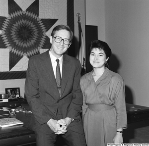 "[""Senator John D. (Jay) Rockefeller sits on the corner of the desk in his office  next to an unidentified young woman.""]%"