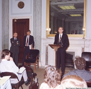 "[""This color photograph shows Senator John D. (Jay) Rockefeller speaking in a room in front of a seated audience.""]%"