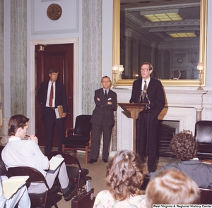 "[""This color photograph shows Senator John D. (Jay) Rockefeller speaking in front of an audience at an event in a Senate building.""]%"