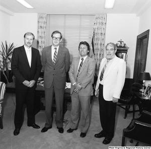 "[""Senator John D. (Jay) Rockefeller stands with three unidentified men in front of the desk in his office.""]%"