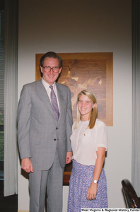 "[""Senator John D. (Jay) Rockefeller stands next to a young woman who appears to be an intern.""]%"