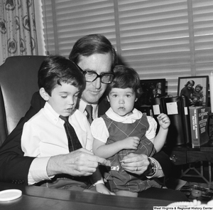 "[""Senator John D. (Jay) Rockefeller holds two small children on his lap as he sits behind his desk.""]%"