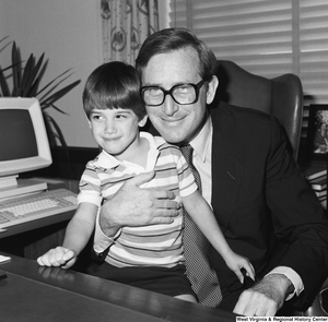 "[""A small unidentified child looks away as Senator John D. (Jay) Rockefeller holds him for a photograph in his office.""]%"
