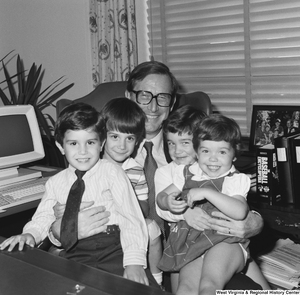 "[""Senator John D. (Jay) Rockefeller holds a group of four unidentified children on his lap as he sits behind the desk in his Washington office.""]%"
