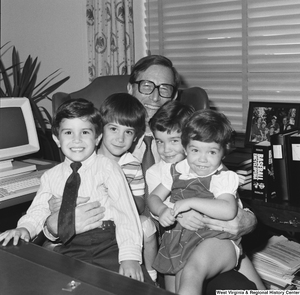 "[""Four unidentified children sit on Senator John D. (Jay) Rockefeller's lap behind the desk in his Washington office.""]%"