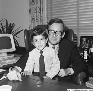 "[""An unidentified boy sits on Senator John D. (Jay) Rockefeller's lap behind the desk in his office.""]%"