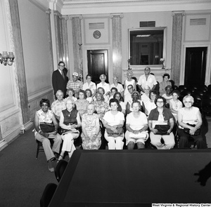 "[""Senator John D. (Jay) Rockefeller stands for a photograph with a large group of senior citizens from Jefferson County, WV in a room in the Russell Senate office building.""]%"