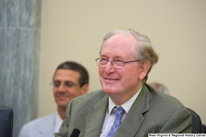 "[""Senator John D. (Jay) Rockefeller smiles at a Commerce Committee hearing.""]%"