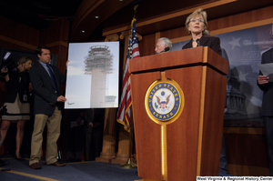 "[""Senator Barbara Boxer speaks at a Commerce Committee hearing. Behind her, a staffer holds a poster board with an image of an airport tower.""]%"