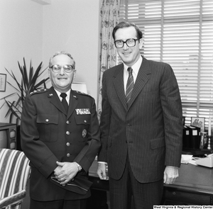 "[""Senator John D. (Jay) Rockefeller stands with an unidentified military officer in his office.""]%"