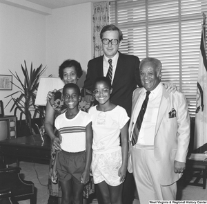 "[""Senator John D. (Jay) Rockefeller stands in his office for a photograph with an unidentified family.""]%"